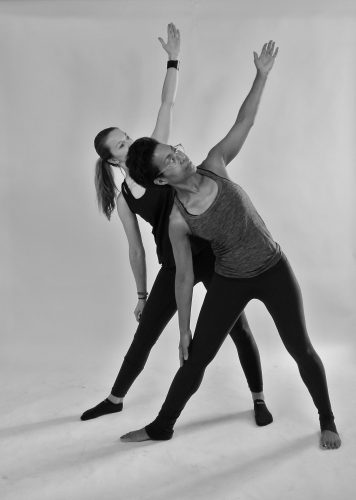 Photograph of 2 woman doing yoga. In front: Xandra, owner of 'Yotopia'