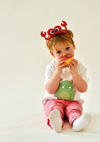 Photo of child with graphic designed t-shirt, sitting on floor eating a cupcake