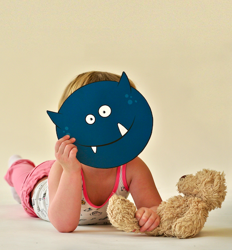 Photography of child holding monster mask (graphic design by SBP)
