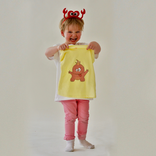 Photography of child holding shirt with monster print (photo and graphic design by SBP)
